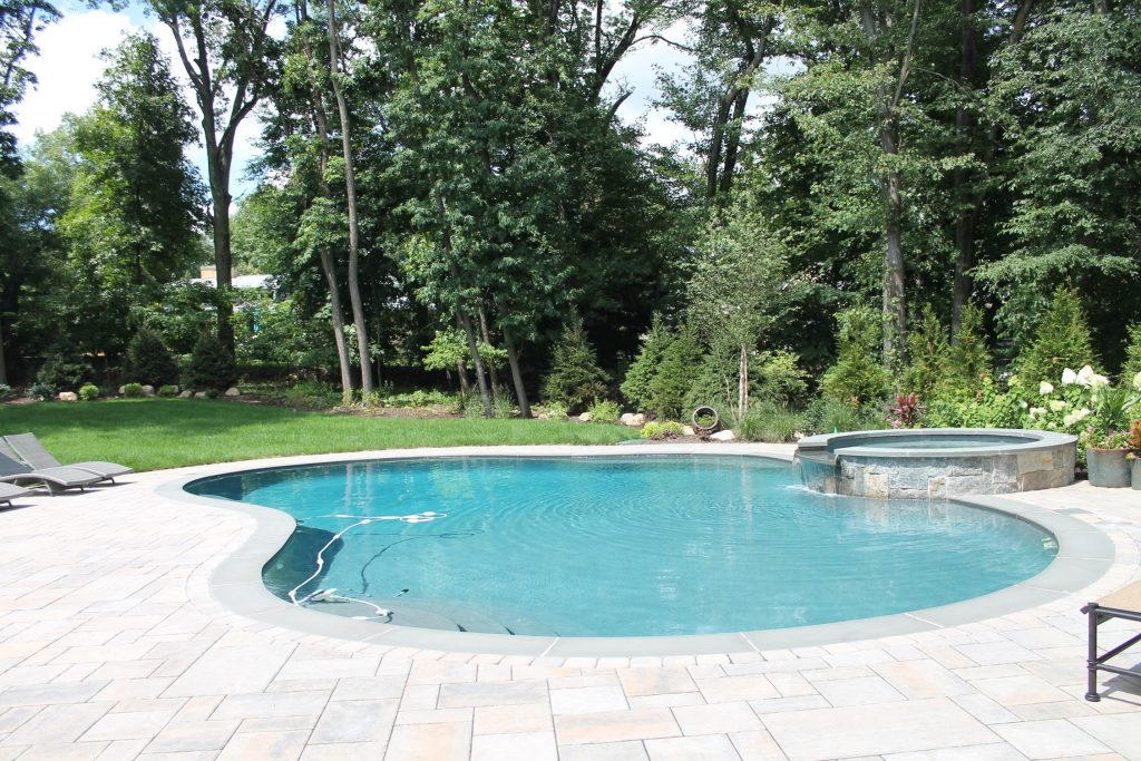 Stone Pool Deck and Spa installed by Curti's Landscaping
